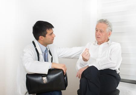 Senior Menschen sprechen über die Symptome zu jungen männlichen Arzt