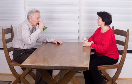 Old couple sitting at dining table and drinking wine photo