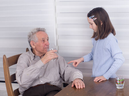 Grandfather communicating with his granddaughter at table