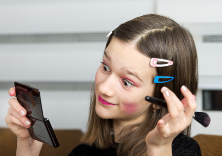 Young girl applying makeup on her face and is satisfied photo