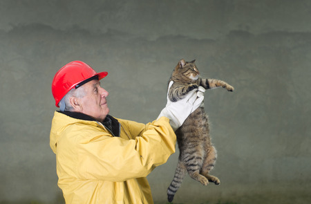 Old man in safety suit holds cat with his arms Stock Photo