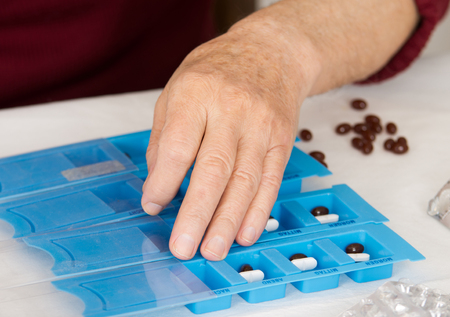 dispense: Males hand sorting drugs in blue pills container Stock Photo