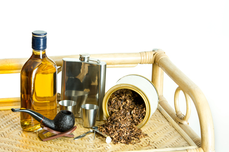 hip flask: Smoking pipe, tobacco, whisky and hip flask on bamboo shelf