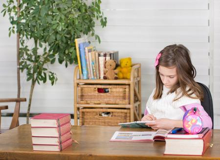 School girl doing homework in her room photo