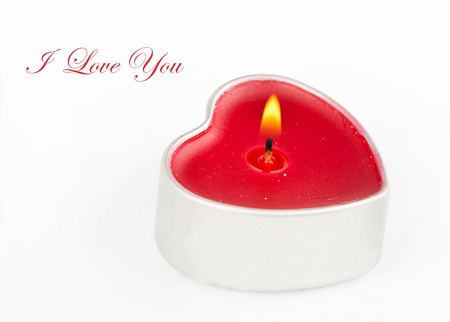 Heart shaped candle with love text on white background photo