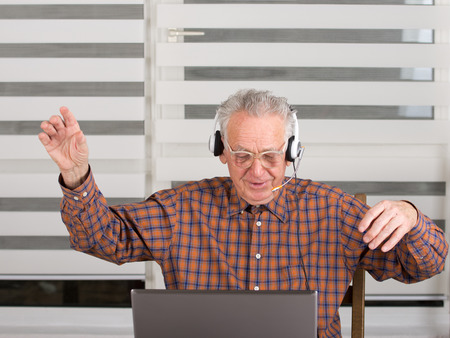 Senior man raised hands up and listen music from laptop photo