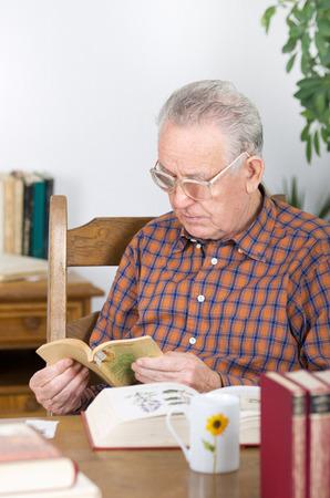 gafas de lectura: Viejo hombre con gafas de leer el libro de lectura en el comedor Foto de archivo