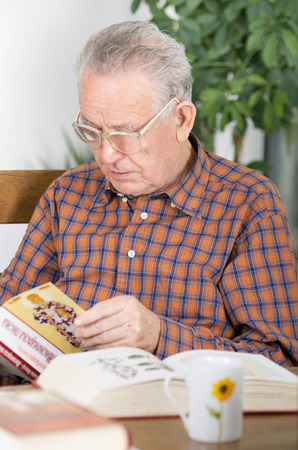 Old man with reading glasses reading book in dining room photo