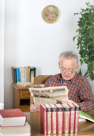 Senior man reading old newspaper from archive in his library photo