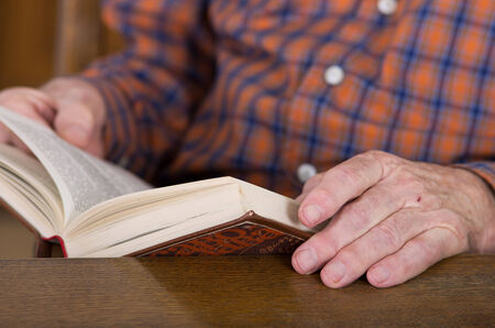 Close up of old mans hands whos reading book photo