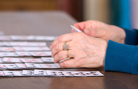 Close up of female hands holding cards and playing solitaire Stock Photo