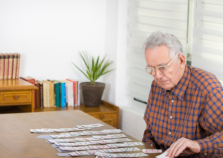 hombre solo: Viejo hombre que juega al solitario con cartas en la mesa de comedor