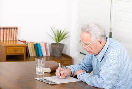 Senior man in pajamas with reading glasses sitting at table and solving crosswords photo