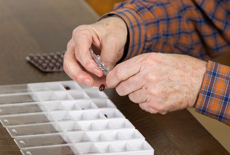 pills in hand: Old man taking out pills from blister into pills box to organize weekly dose