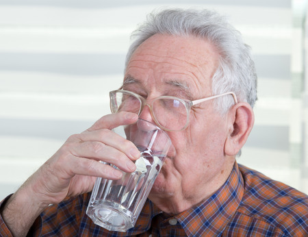 Old man with reading glasses holds and drinks glass of water Stock Photo