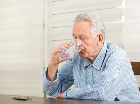 Old man in pajamas drinking glass of water and have pills blister on table photo