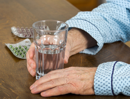 Patients hand holding glass of water and blister with medicals on table photo