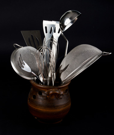 Metal kitchen utensils in pot isolated on black