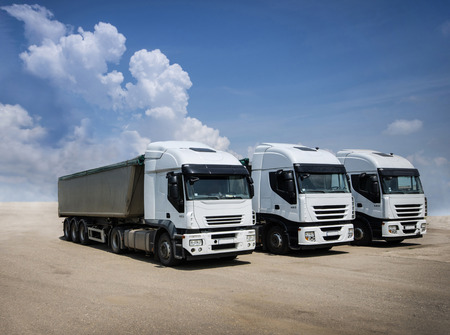 Three white trucks parked on sand with blue sky and white clouds in background photo