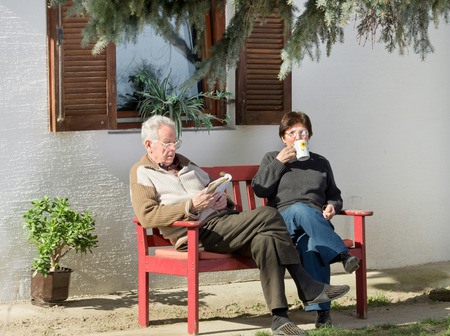 Senior couple sitting on bench in courtyard and reading and drinking coffee photo