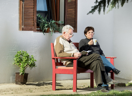 Senior couple sitting on bench in courtyard and enjoying reading and drinking coffee photo
