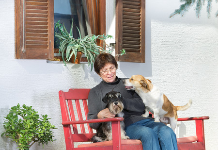 Older woman sitting in courtyard with her dogs in lap photo