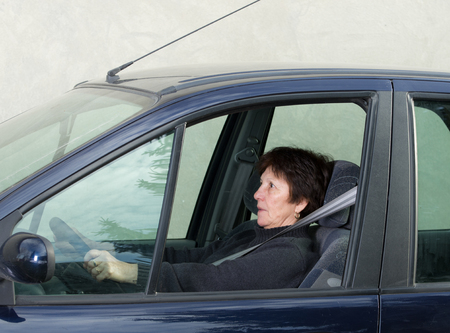 Woman driving car and has scared look photo