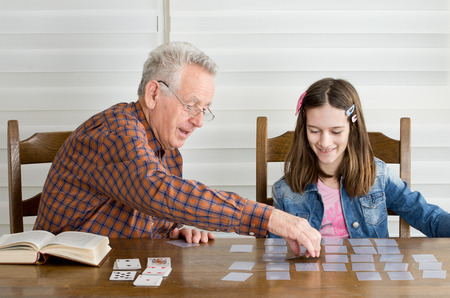Grandpa and granddaughter playing memory game with cards