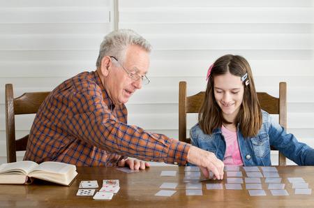 Opa en kleindochter spelen memory spel met kaarten Stockfoto
