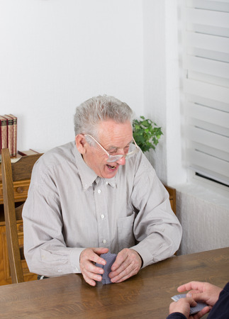 Old man is very excited of playing cards photo