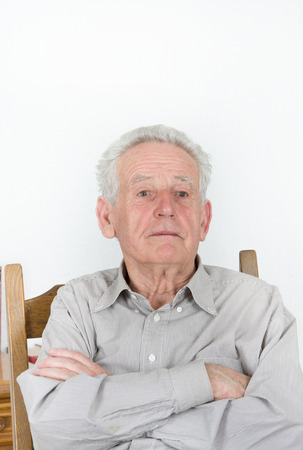 Portrait of angry and too proud old man with crossed arms photo