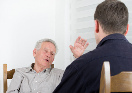 Old man with arm in the air telling stories to young man
