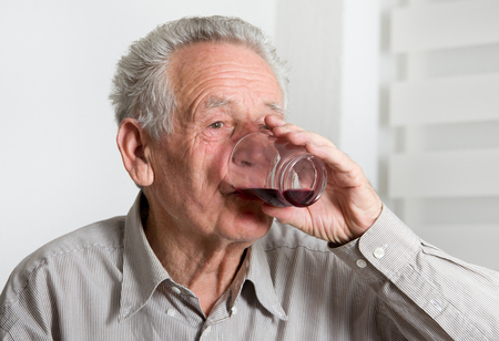 Close up of old man drinking blueberry juice photo