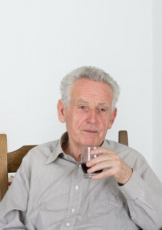 Old man with gray hair holds glass with wine in front of face photo