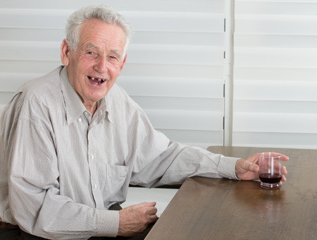 dring: Old man holding glass with alcohol dring and laughing laudly Stock Photo