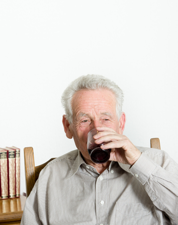 Old man with gray hair in shirt drinking alcohol drink photo