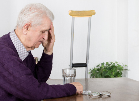 Old man with headache sitting at table and has medications on table photo