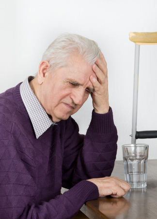 Worried old man sitting at table and holding head photo