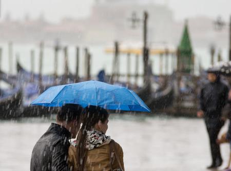 Pareja con un paraguas caminando en la lluvia pesada en la costa de Venecia
