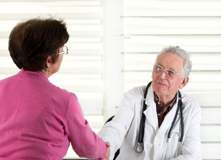 Senior doctor shaking hands with older female patient photo