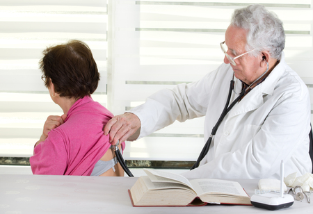 Senior doctor listening patients heartbeat with stethoscope photo