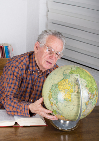 Old man holding globe and looking for travel destination photo