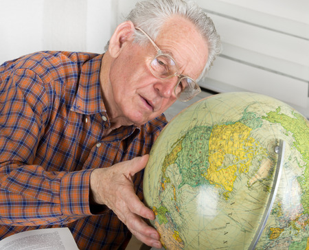 Old man looking very seriously at globe photo