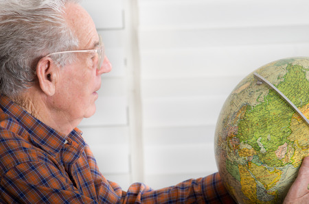Close up of old man with reading glasses looking at globe photo