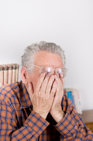 Old man holding hands on eyes under reading glasses photo