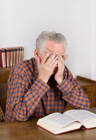 Tired old man holding hands on eyes after reading a book photo