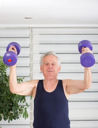 loose skin: Senior man in his seventies training and lifting weight Stock Photo