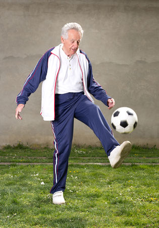 Old man in seventies kicking a soccer ball in courtyard photo