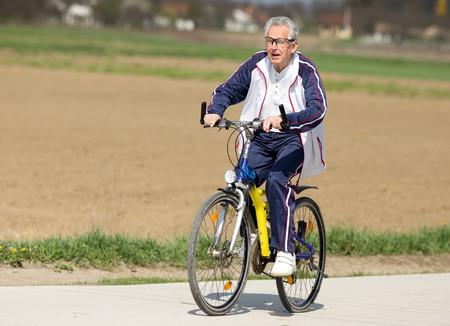 vestidos antiguos: Hombre mayor activo que monta una bicicleta en campo Foto de archivo