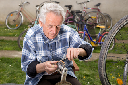 Bicycle mechanic repairing bicycle pedal in courtyard photo